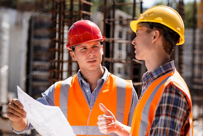 Civil engineer and construction manager in orange work vests and hard helmets explore construction