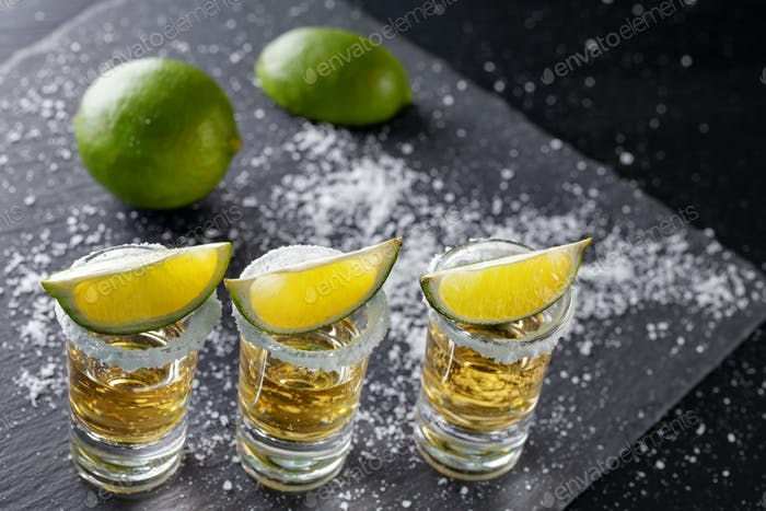 Three glasses of golden Mexican tequila and lime with salt