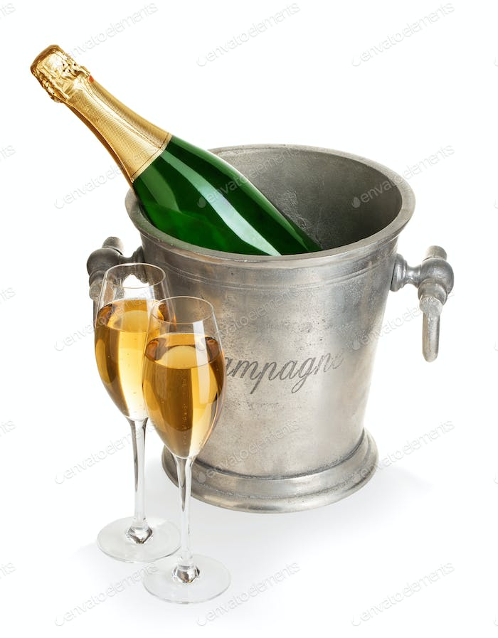 Champagne bottle in ice bucket with glasses of champagne isolated.