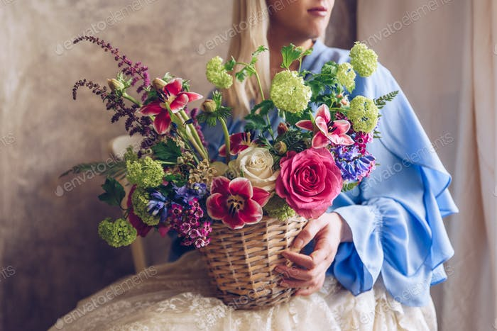 Young woman holding basket with flowers. Vintage, romantic conce
