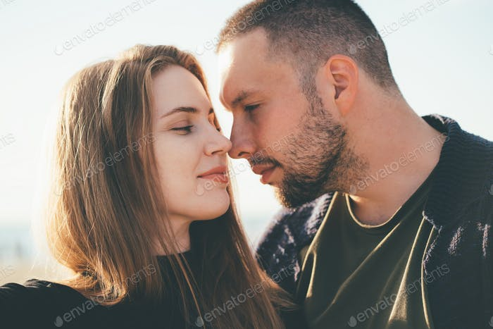 Happy couple in love. Beautiful man and woman look at each other tenderly, close-up portrait