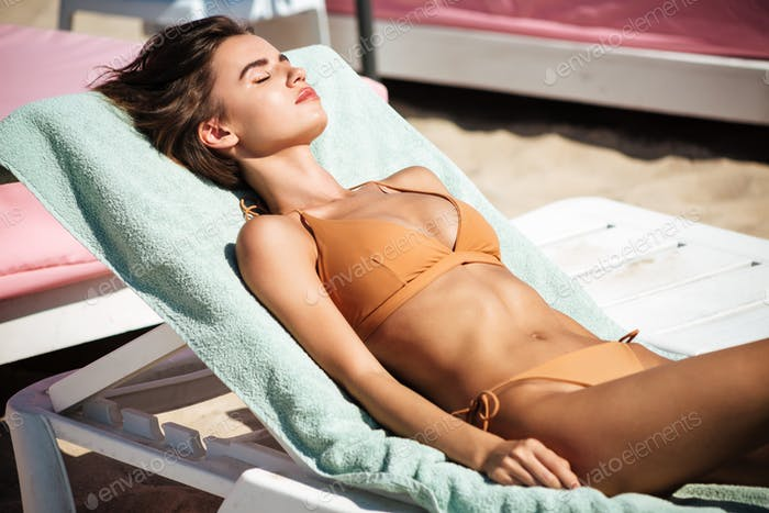 Beautiful girl in bikini lying on deck chair with closing eyes while spending time on beach