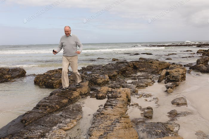 Far sight of active senior man walking on the rock at beach