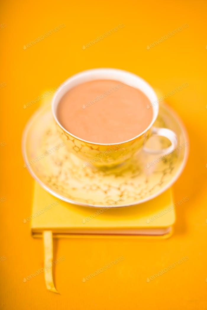 Tasse und Untertasse und Kaffee mit Milch auf einem gelben Hintergrund