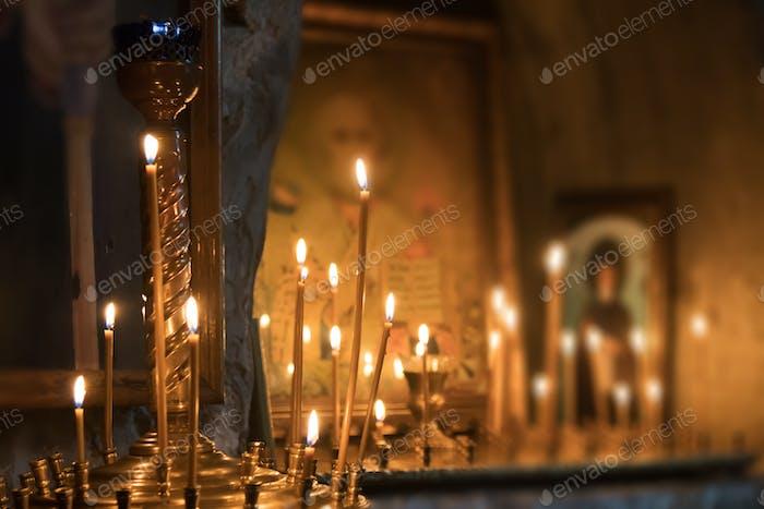 Icons und brennende Kerzen in der Kirche