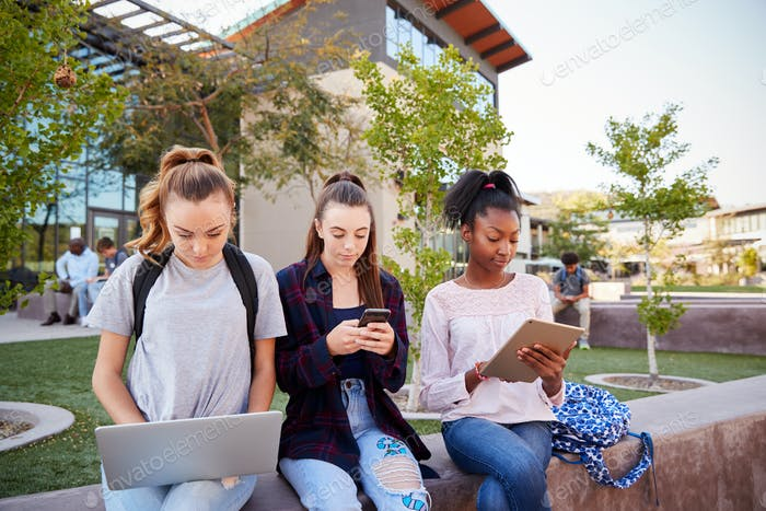 Female High School Students Using Digital Devices Outdoors During Recess
