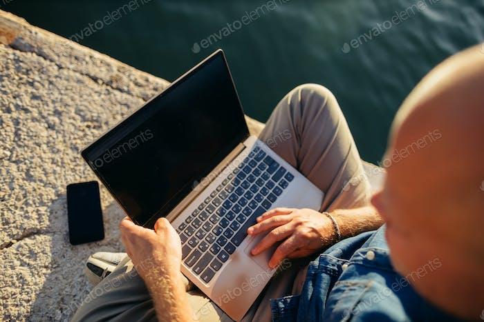 Freelancer Browsing Laptop am Strand bei Sonnenuntergang