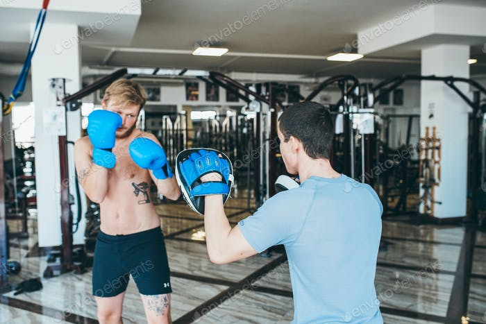 Men practicing boxing in gym
