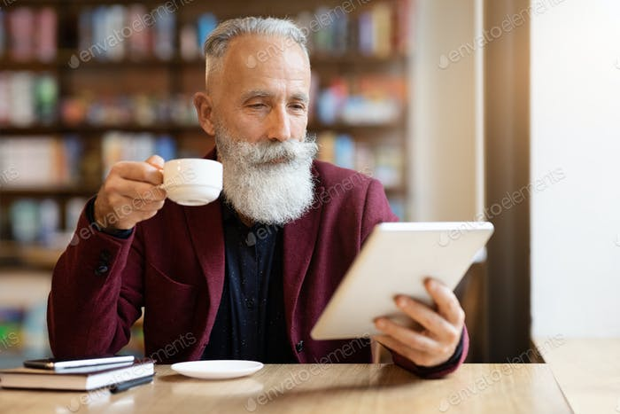 Wealthy grey-haired elderly man drinking coffee and using digital tablet