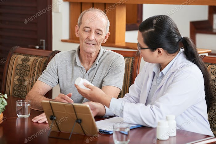 Doctor with tablet showing pills to patient
