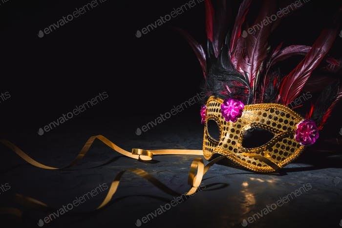 Golden carnival mask with golden ribbon on black background