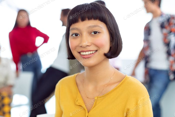 Front view of happy young Asian businesswoman looking at camera in a modern office