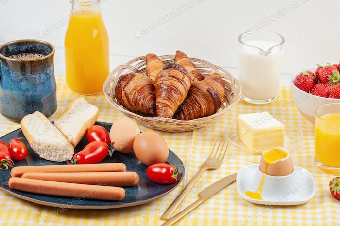 Breakfast served with coffee, croissants, sausages, eggs, fresh berries, milk, butter, orange juice