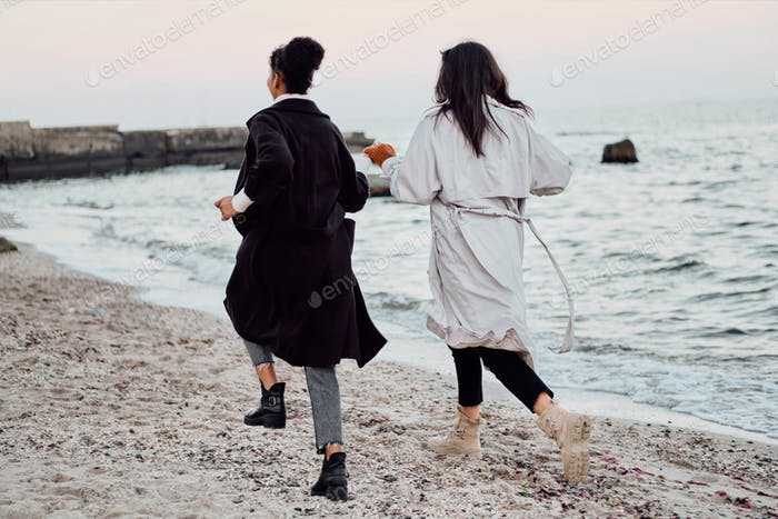 Back view of two attractive stylish girls in trench coats happily running by the sea