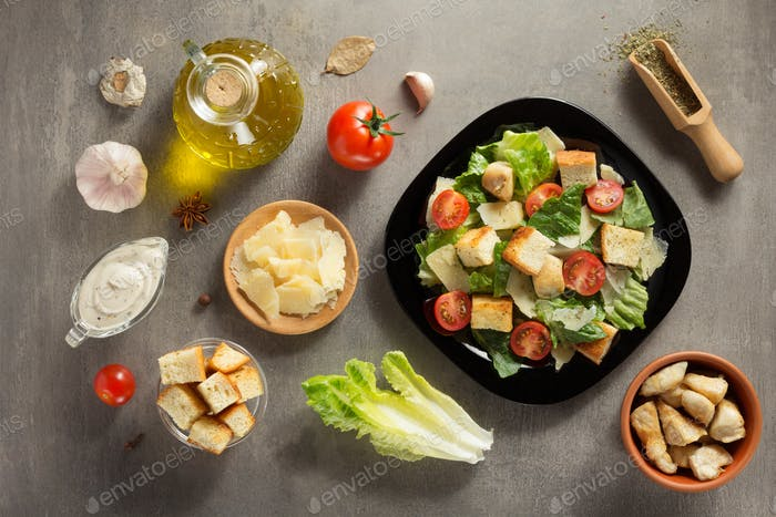 caesar salad and ingredients at table