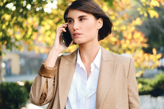 Young beautiful stylish businesswoman thoughtfully talking on cellphone outdoor
