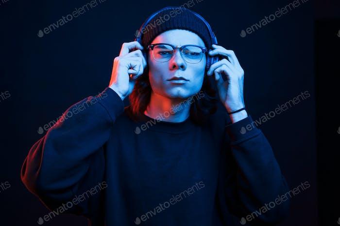 Listening to the music. Studio shot in dark studio with neon light. Portrait of serious man