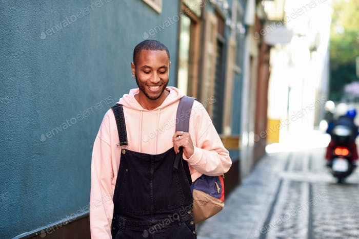 Young black man walking smiling down the street.