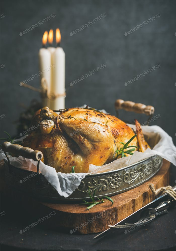 Christmas holiday table set with roasted whole chicken and candles