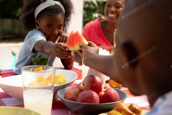 African American girl playing with slices of watermelon during a family lunch in the garden
