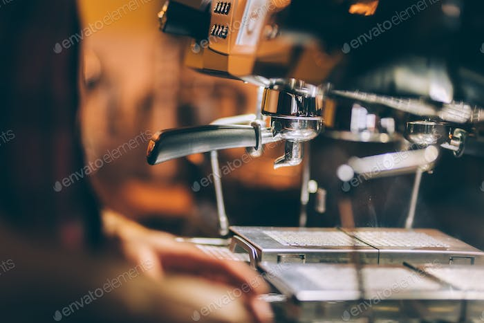 Professional barman preparing fresh espresso with industrial coffee machine