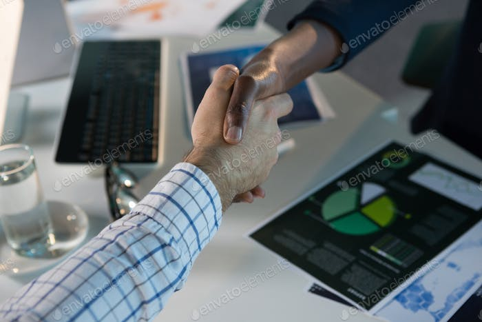 Executives shaking hands at desk