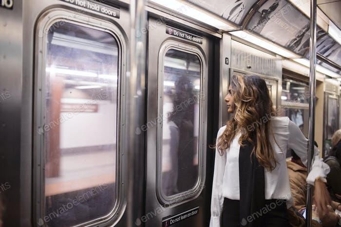 Geschäftsfrau Blick durch das Fenster während der Fahrt in der U-Bahn Zug