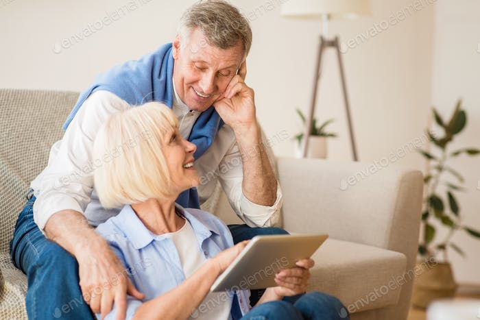 Happy elderly couple searching film on digital tablet