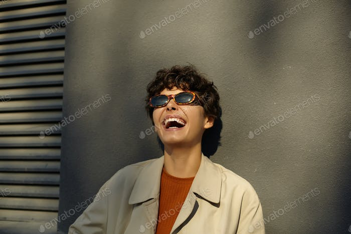 Outdoor shot of joyful pretty brunette female with casual hairstyle laughing happily