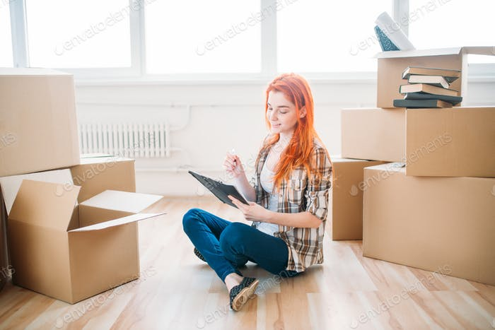 Woman sitting on the floor among cardboard boxes