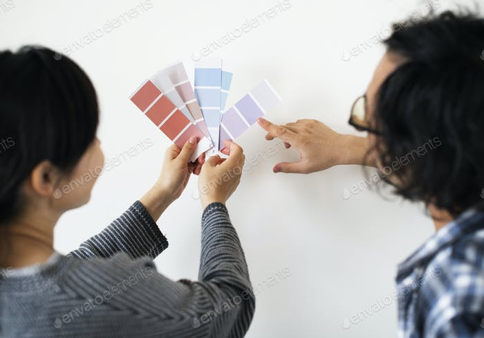 Asian couple choosing wall color