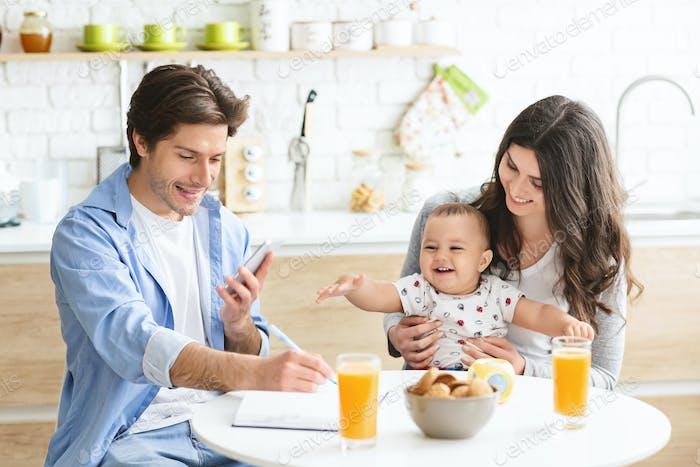 Hombre joven mensajes de texto en el teléfono celular, cena con su esposa y bebé