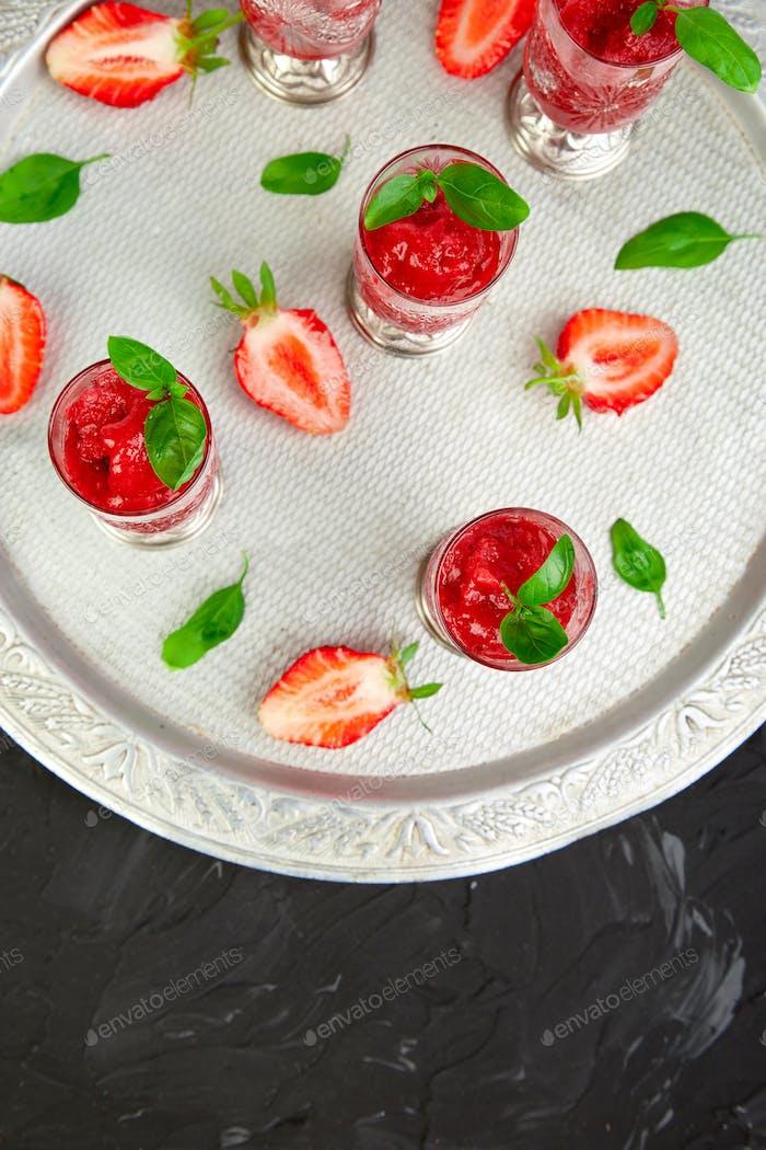 Summer refreshing strawberry sorbet, slush granita drink in serving glasses.