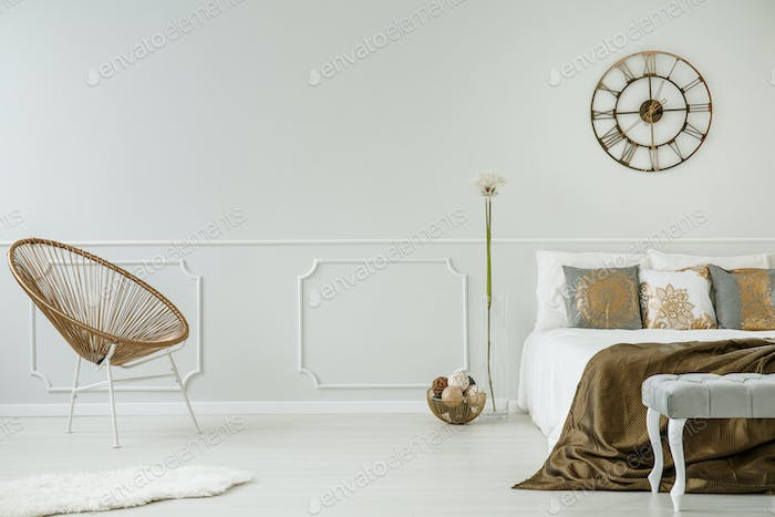 Big clock hanging on light grey wall with wainscoting in real ph