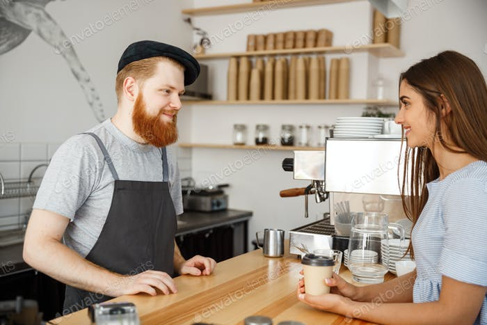 Coffee Business Concept - young beared handsome barista talking with beautiful caucasian customer in