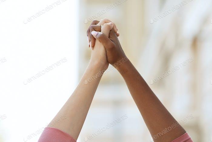 Unrecognizable black and caucasian ladies holding hands