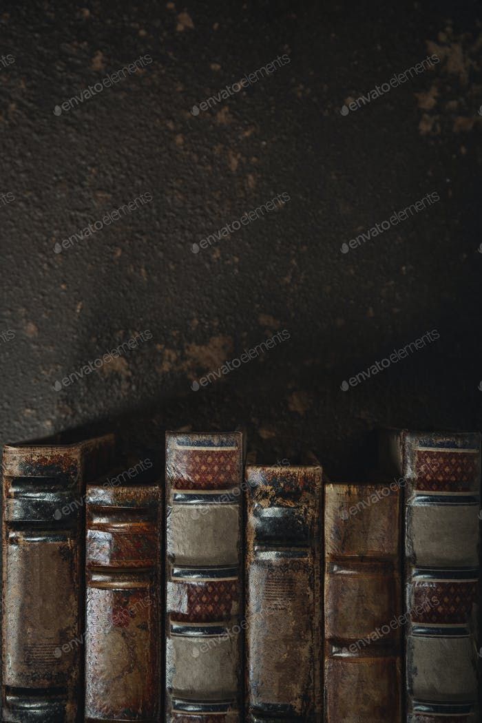Old fashioned flat lay with stack of antique leather bound books against a dark background