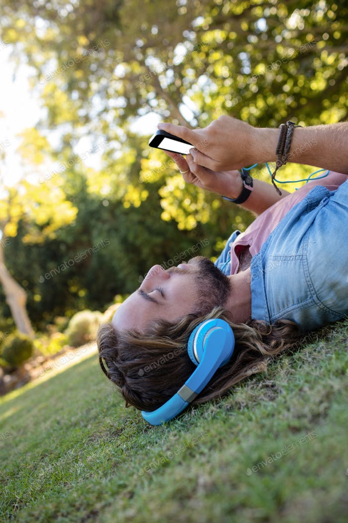 Man listening to music and using mobile phone while lying on grass