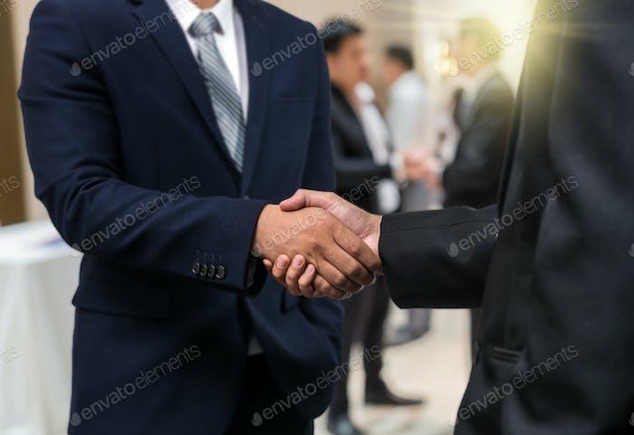 Бизнес пожимает руку партнеру над размытым фото группы Businessman Корпоративный