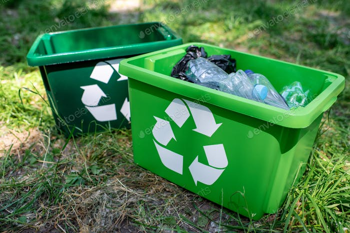 green recycling boxes with plastic trash standing on lawn