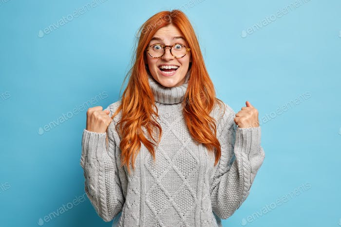 Joyful redhead young woman with cheerful expression rejoices success clenches fists after achievemen