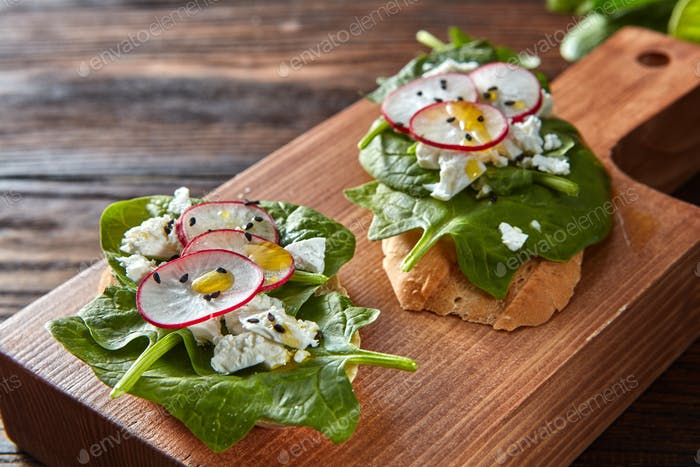 Ciabatta toasts with soft cottage cheese, slices of radish, fresh spinach, flax seeds on wooden