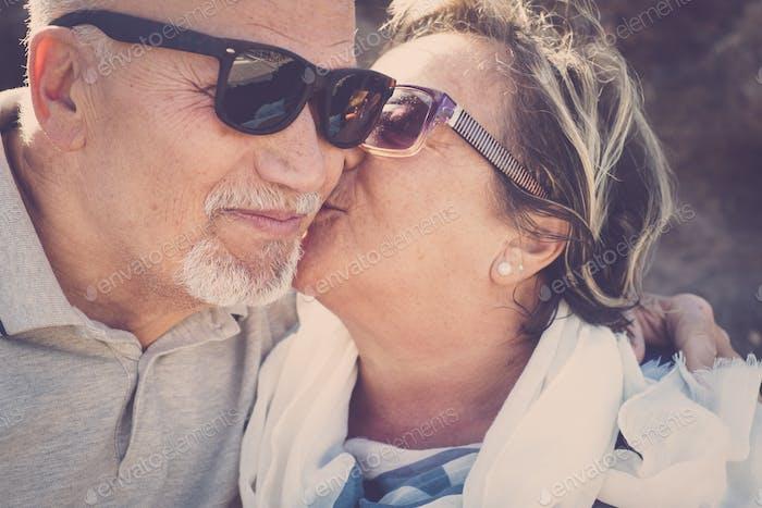 zwei Senioren mit Sonnenbrille küssen sich