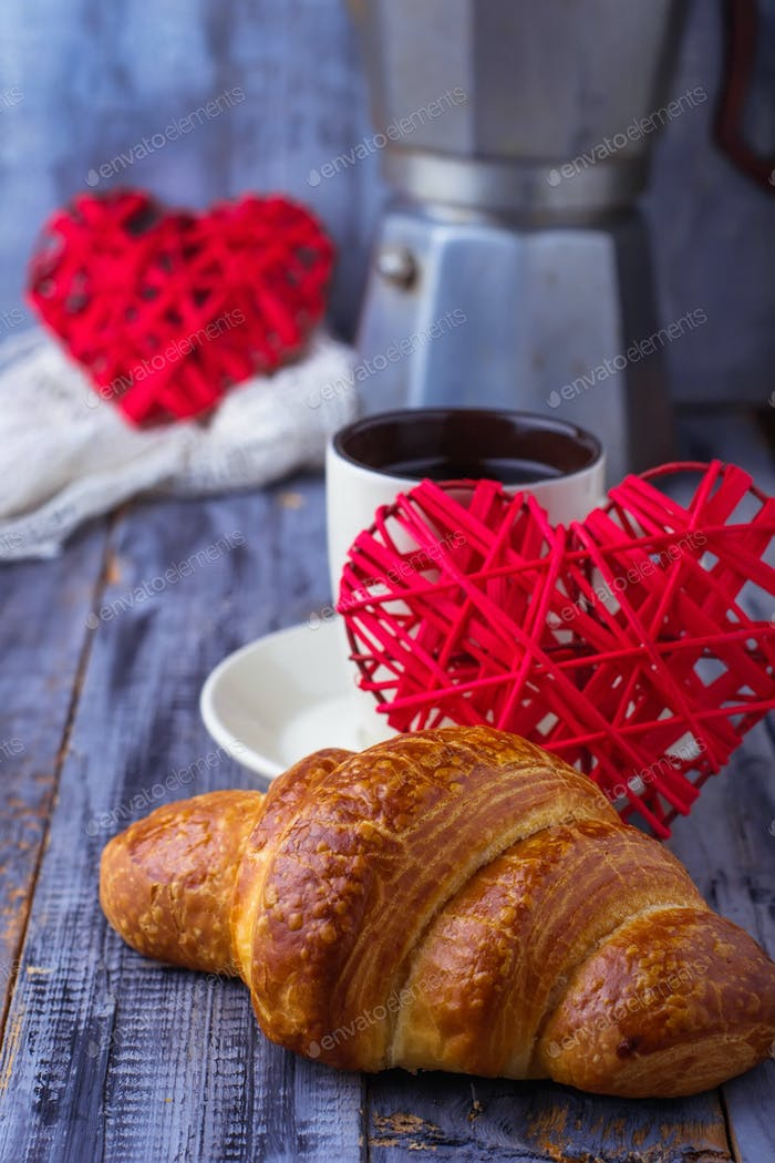 Croissant, coffee and heart on wooden background