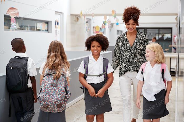 Teacher And Pupils Walking Along Corridor In Busy Elementary School Corridor