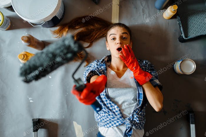 Female house painter lies on the floor, top view