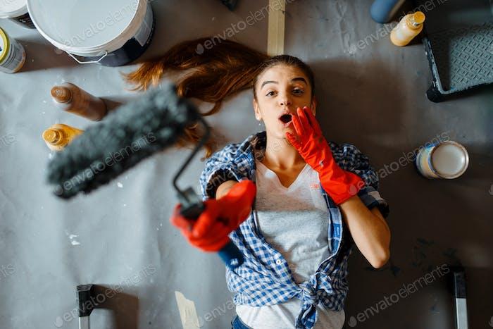Weibliche Hausmalerin liegt auf dem Boden, Blick von oben