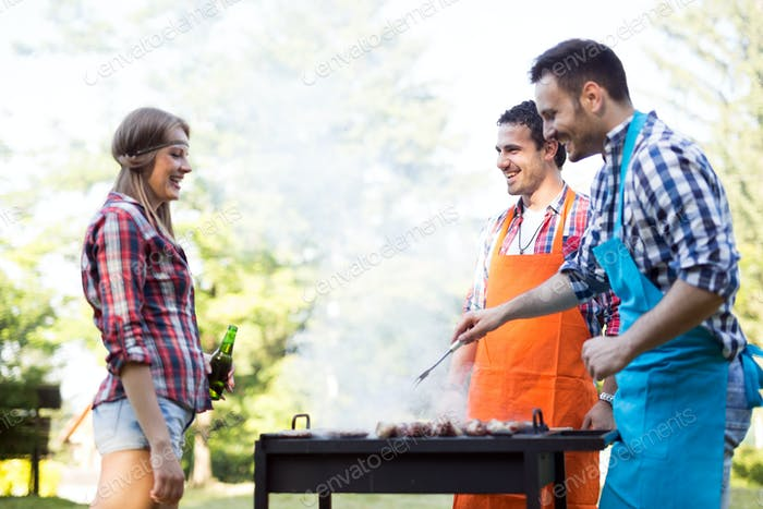 Friends enjoying bbq party in a forest and smiling