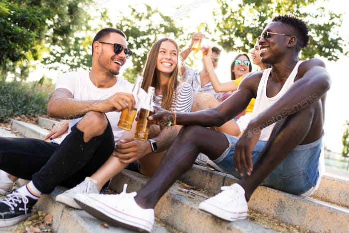 Group of young people toasting with beer in an urban area.