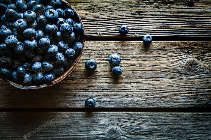 Fresh blueberries in the bowl on a wooden table. Top view. Fruits, food